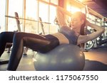 young fit woman doing sit ups... | Shutterstock . vector #1175067550