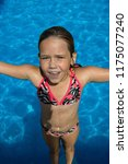 small girl in the swimming pool. | Shutterstock . vector #1175077240