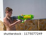 the boy play with water gun in... | Shutterstock . vector #1175077249