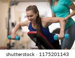 personal trainer helping pretty ... | Shutterstock . vector #1175201143