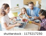 busy young mom typing on laptop ... | Shutterstock . vector #1175217250