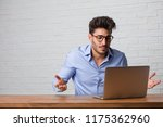 Small photo of Young business man sitting and working on a laptop doubting and shrugging shoulders, concept of indecision and insecurity, uncertain about something