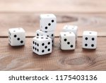 white dice on brown wooden table | Shutterstock . vector #1175403136