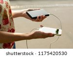 girl with phone and power bank | Shutterstock . vector #1175420530