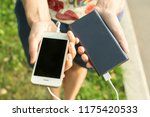 girl holds a phone and an power ... | Shutterstock . vector #1175420533