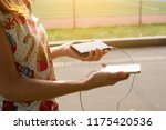 girl holds a phone and an power ... | Shutterstock . vector #1175420536