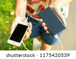 girl with phone and power bank | Shutterstock . vector #1175420539