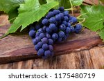 Bunch of blue Isabella grapes on a wooden board