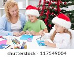 Family around christmas time making greeting cards wearing santa hats - stock photo