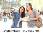 happy girl helping to a tourist ... | Shutterstock . vector #1175569786