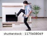 man trying to fix broken tv | Shutterstock . vector #1175608069