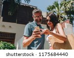 couple using their phone while... | Shutterstock . vector #1175684440