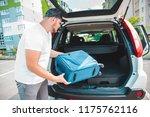 man putting bags in car trunk.... | Shutterstock . vector #1175762116