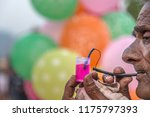 old indian street vendor blows... | Shutterstock . vector #1175797393