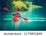 Glacial Lake Kayak Trip. Caucasian Tourist Paddling in the Red Kayak. - stock photo
