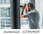 Stock photo depressed bearded man leaning at window and looking through it 1175929039