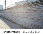 brick fence with barbed wire... | Shutterstock . vector #1176167110