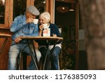happy senior couple sitting at... | Shutterstock . vector #1176385093