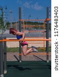 Small photo of Girl on street workout. Young slender woman wring out on parallel crossbeams. She is dressed in sportswear. Healthy lifestyle.
