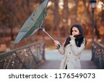 girl fighting the wind holding... | Shutterstock . vector #1176549073