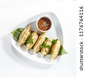 Small photo of Oriental Fried Dim Sum with Minced Meat also known as Gyoza, Dim Sum, Jiaozi or Momo on a Banana Leaf with Spicy Sauce Top View. Hot Crunchy Deep-Fried Beef and Mutton Dimsum Isolated on White
