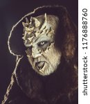 Small photo of Monster with sharp thorns and warts on face. Alien or reptilian makeup. Demon in fur coat on black background. Horror and fantasy concept. Man with dragon skin and grey beard.