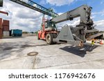 red forklift in a container port | Shutterstock . vector #1176942676