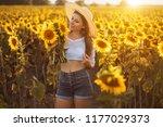 cute brunette in a blossoming... | Shutterstock . vector #1177029373