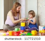 Happy pregnant mother plays with child in home interior - stock photo