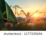 Happy woman with open arms stay near tent around mountains under sunset light sky enjoying the  leisure and freedom. - stock photo