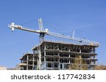 Large construction crane working on high rise - stock photo