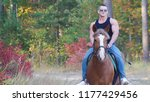 Small photo of A strong man with a powerful body in a black t-shirt in sunglasses rides a horse