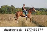 Small photo of A strong man in a t-shirt of black color, in denim pants and sunglasses riding a horse in nature