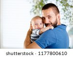 happy young father holding his... | Shutterstock . vector #1177800610