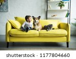 Stock photo happy child sitting on yellow sofa with pets 1177804660