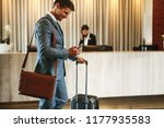 Stock photo businessman standing in hotel lobby with suitcase and using his mobile phone male business 1177935583