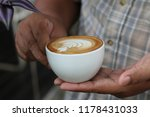 man holding a cop of coffee in... | Shutterstock . vector #1178431033
