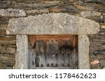 Small photo of Front view of granite frame and vintage wooden door in old stone facade