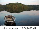 Small photo of beautiful photo with lake view with almost smooth water, tied boat, forest on the other side, reflection of the sky in the water, pink blue shades, evening