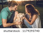 Stock photo happy couple with puppy dog in the country couple in a sunset with puppy dog 1179293740