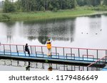 People, men are fishing from the pontoon, apron, bridge on the lake with ducks at the recreation center, sanatoria in the fall.