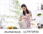young woman in kitchen cooking...   Shutterstock . vector #117973954
