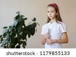 a cute girl is sitting at a... | Shutterstock . vector #1179855133