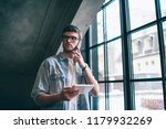 pensive male user in spectacles ... | Shutterstock . vector #1179932269