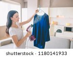 woman is steaming blue shirt in ... | Shutterstock . vector #1180141933