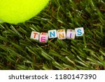 Small photo of The word tennis is made up of cubes with colored letters lying on the green grass next to the tennis ball