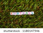Small photo of The word football is made up of cubes with colored letters lying on an artificial green grass