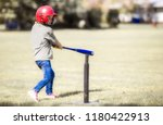 Small photo of A six year old girl wearing jeans and t-shirt with a red batting helmet gritting her teeth as she hits the ball off the T ball stand on green grass