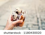 tourist holds in hand fritule ... | Shutterstock . vector #1180430020