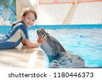 kid and dolphin. playing... | Shutterstock . vector #1180446373